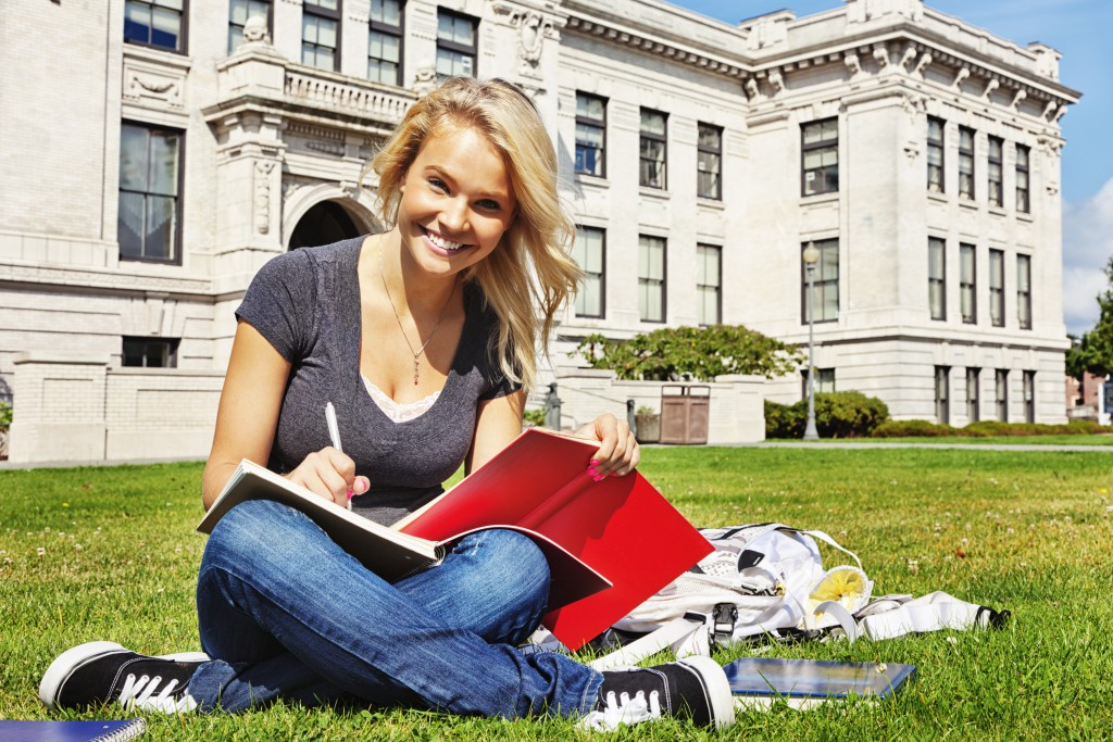 Student studying on college lawn